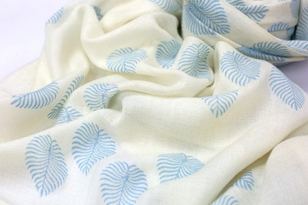 Close up detail of pale blue little woodland fern on a white beautiful background, this woodland fern print cashmere shawl is the perfect accessory.
