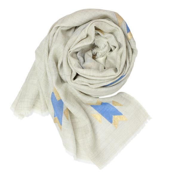 Rolled up Navajo scarf. Cashmere scarf with hand block printed Navajo design in a kingfisher blue with gold on a neutral background.