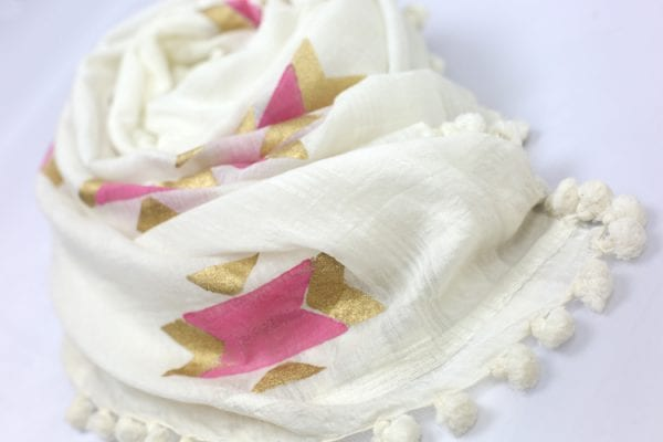 Close up of white scarf with stunning pink and gold pattern