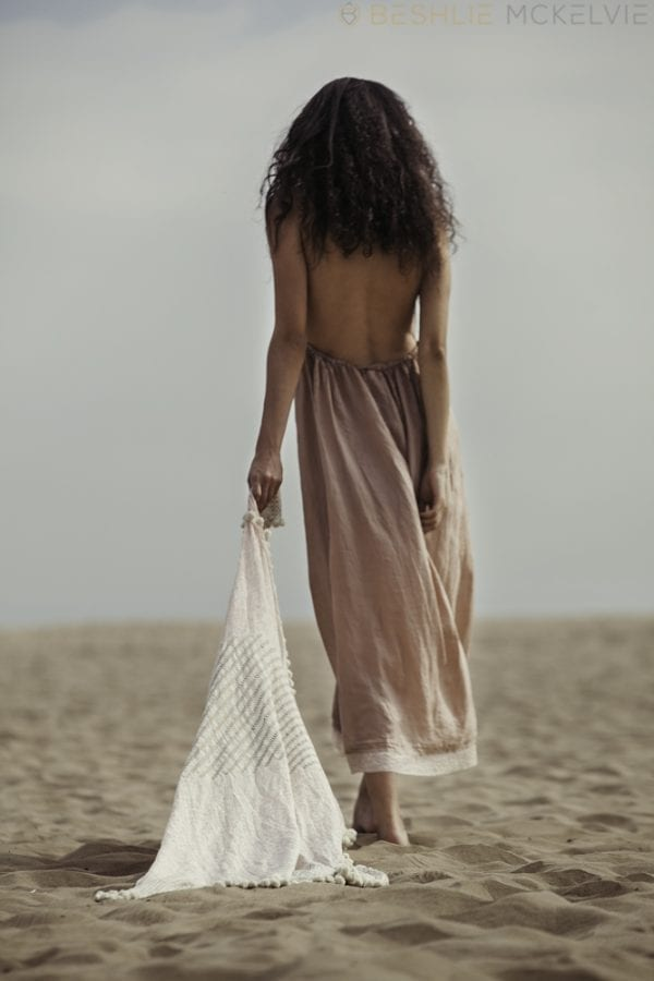Model walks on beach holding fairy tales dupatta will bring your story to life! Stunning hand woven & hand printed in gold & pinks, made with a blend of cotton & silk.