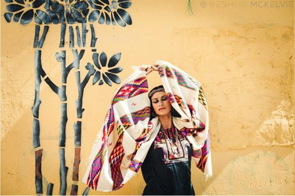 Model holding overhead the Himalaya hand woven wool shawl is a rainbow of color on a cream with hand woven luxurious merino wool that can be styled in a number of ways.