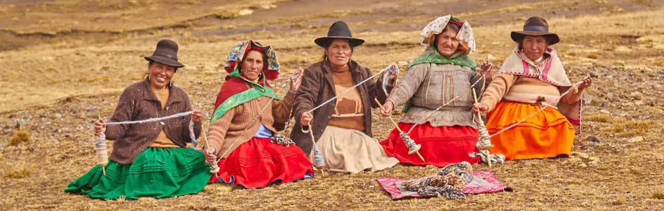 Peruvian ladies in traditional clothing sit outside making yarn