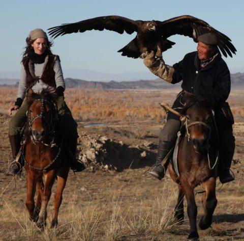 Beshlie rides alongside an eagle hunter in MOngolia
