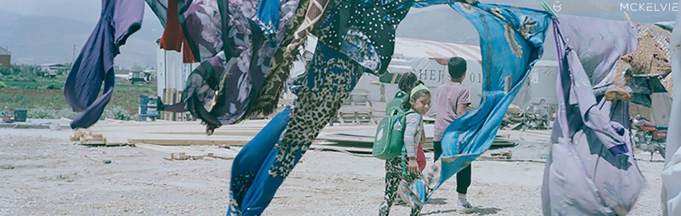 Syrian girl walks underneath flowing scarfs