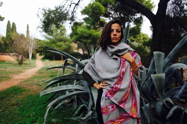 Model wearing Himalaya hand woven wool shawl is a rainbow of color on a muted green with hand woven luxurious merino wool that can be styled in a number of ways.