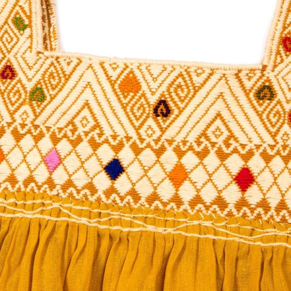 Close up detail of embroidery. This mustard Mexican Peasant mini dress for children has beautiful hand embroidery beautifully around the neck and cute hanging tassels at the sleeves.