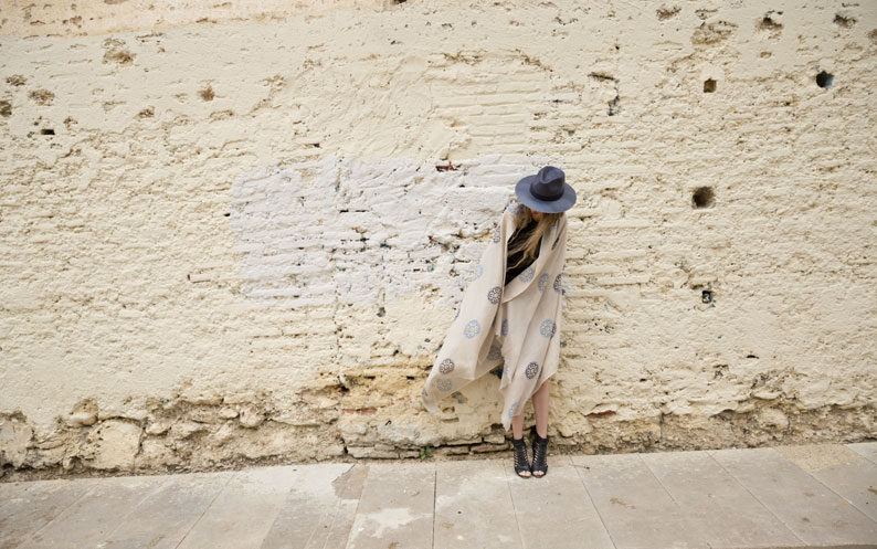 Model stands against wall wearing Sustainable fashion scarf from Beshlie