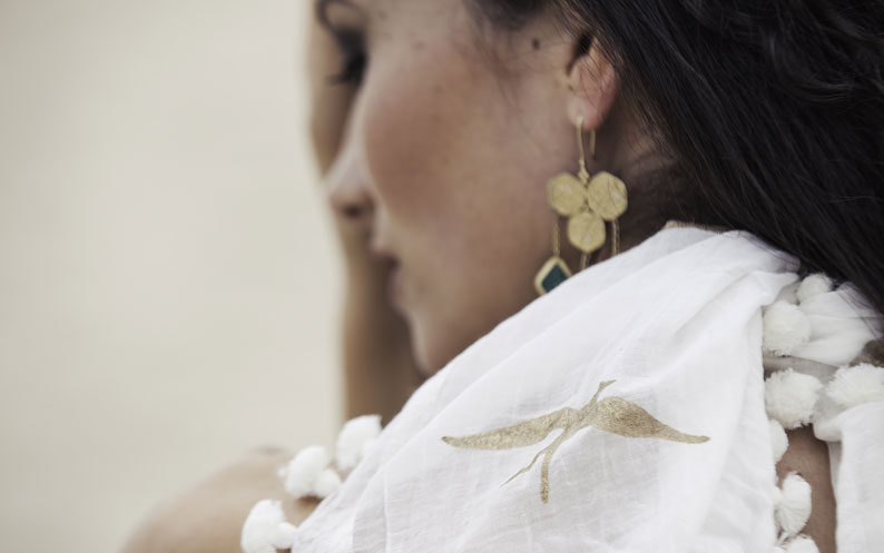 Close up of model wearing gold swallow design scarf on white