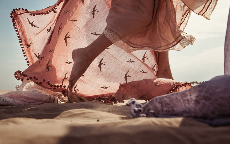 Feet in the sand with scarf flowing