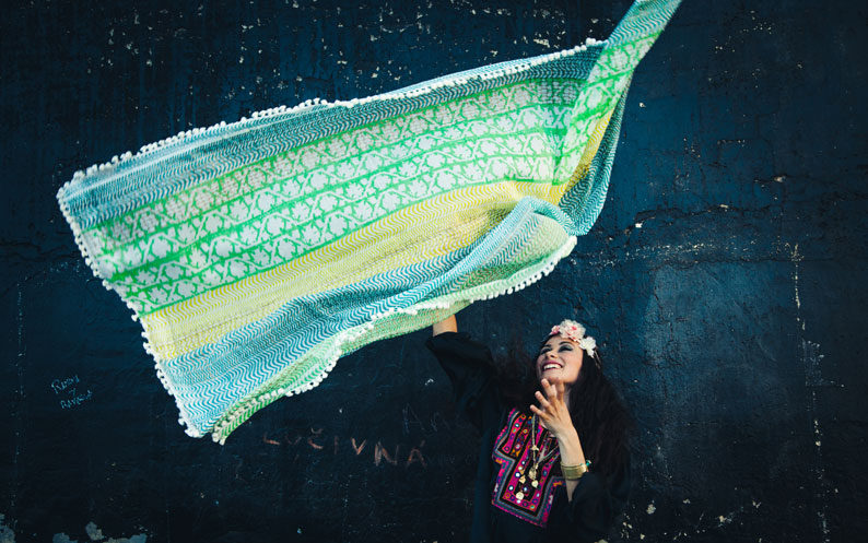 Model throws green patterned scarf into the air