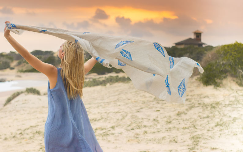 Model holds flowing fair trade scarf in the wind