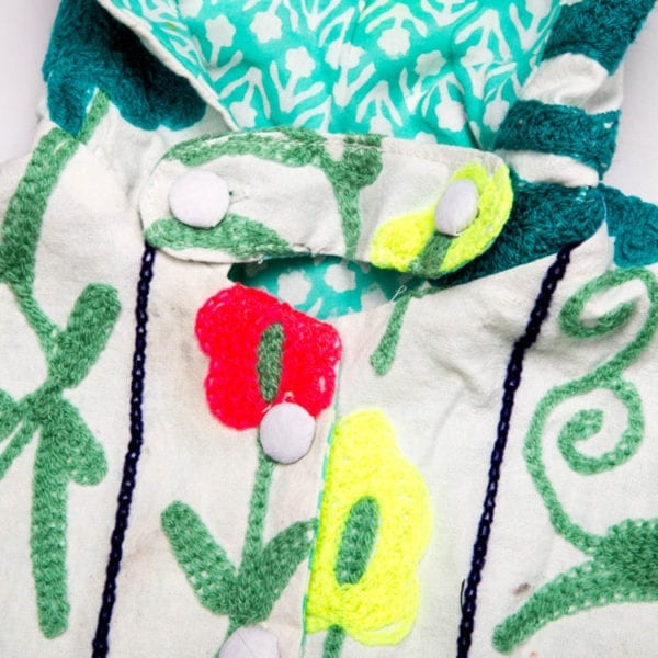 Close up detail of Suzani, a children's Cape created by block printing and hand embroidery. Bright, colourful pattern and a cotton lining. From Beshlie Mckelvie.