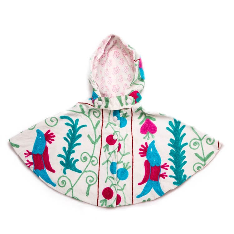 Shop for the Suzani, a children's Cape created by block printing and hand embroidery. Bright, colourful pattern in blue and purple and a cotton lining. From Beshlie Mckelvie.