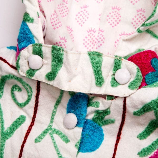 Close up detail of Suzani, a children's Cape created by block printing in blue and purple and hand embroidery. Bright, colourful pattern and a cotton lining. From Beshlie Mckelvie.