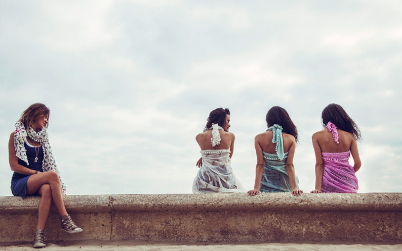 Models sit on a wall wearing different Beshlie Mckelvie scarfs and shawls