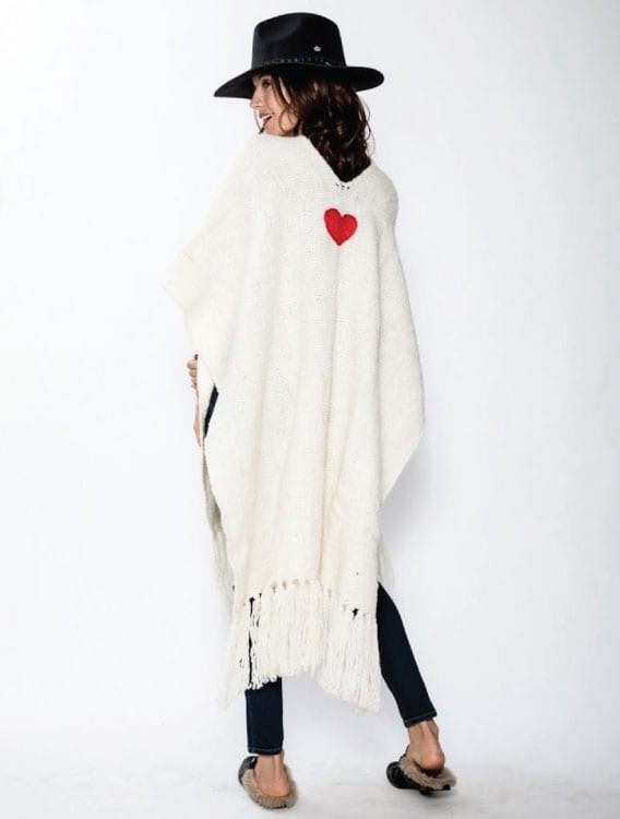 Model wearing the Corazon Poncho is Hand loomed by artisans in Argentina with 100 % Natural wool. Stunning design with neutral background and heart detail. From Beshlie Mckelvie.