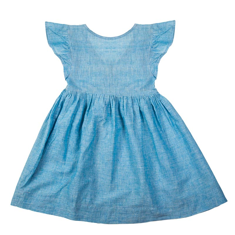 Classic style mini nomadic dress hand loomed in Khadi cotton. This cornflower girls dress has a tie at the back, frill sleeves & mother of pearl buttons. From Beshlie Mckelvie.