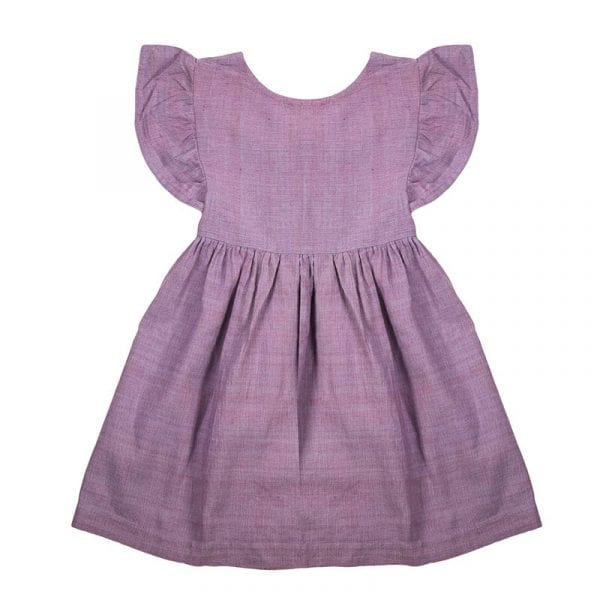 Classic style mini nomadic dress hand loomed in Khadi cotton. This lavander girls dress has a tie at the back, frill sleeves & mother of pearl buttons. From Beshlie Mckelvie.