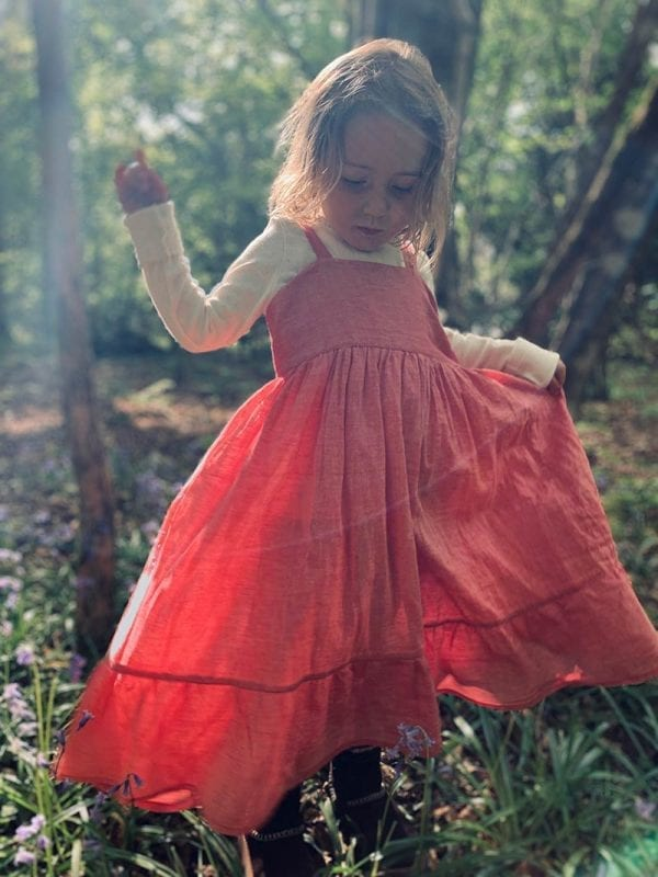 Little girl explores the woods in her classic style mini nomadic toddlers dress. Hand loomed in Khadi cotton. Meadow sweet rose is our cute dress, perfect for summer meadow picnics & beach days. From Beshlie Mckelvie.