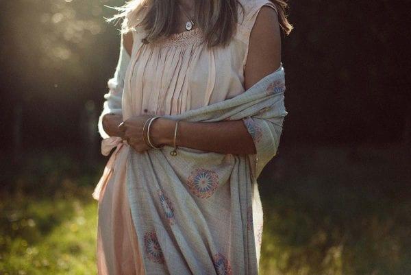 Exquisite Mandala Scarf fair trade cashmere shawl from Beshlie Mckelvie worn in sunny field.