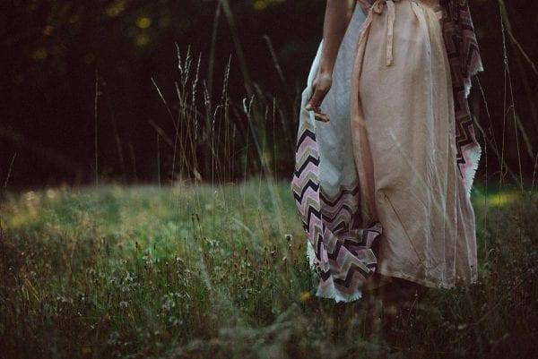 Model walking through field holding beautiful Calli scarf