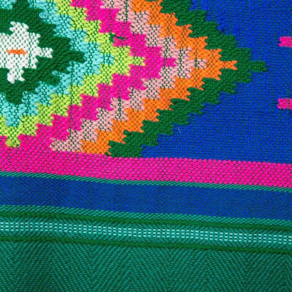 Close up detail of the stunning green handwoven scarf with a colourful Aztec motif. In the Nahuatl Aztec language, Totec is the God of spring, representing the renewal of seasons.