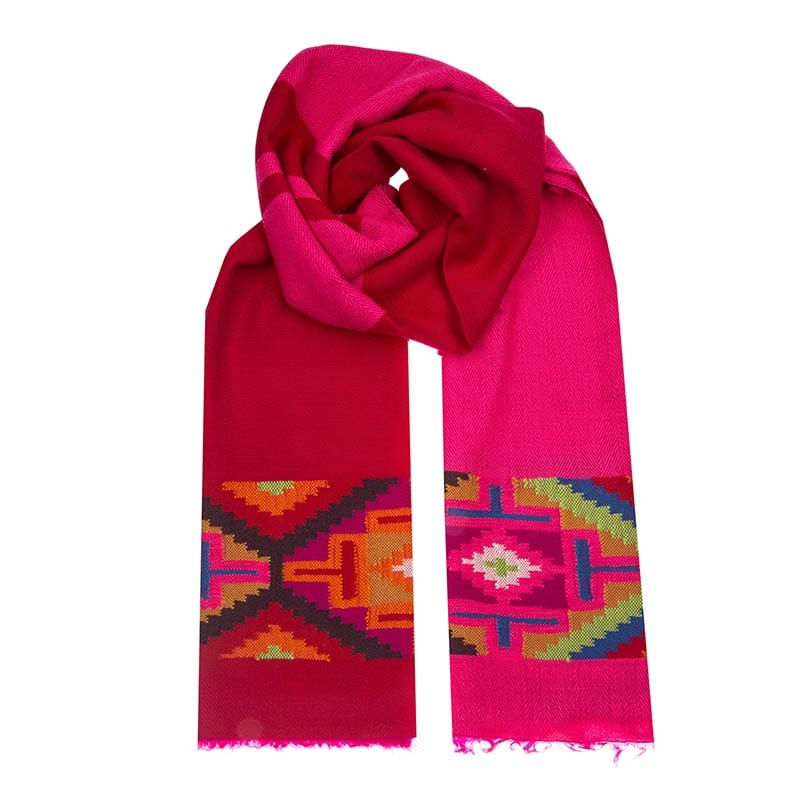 Soft and versatile pink and red scarf with Aztec patterning. Traditionally hand woven in South America, these scarves tell the story of culture & heritage.