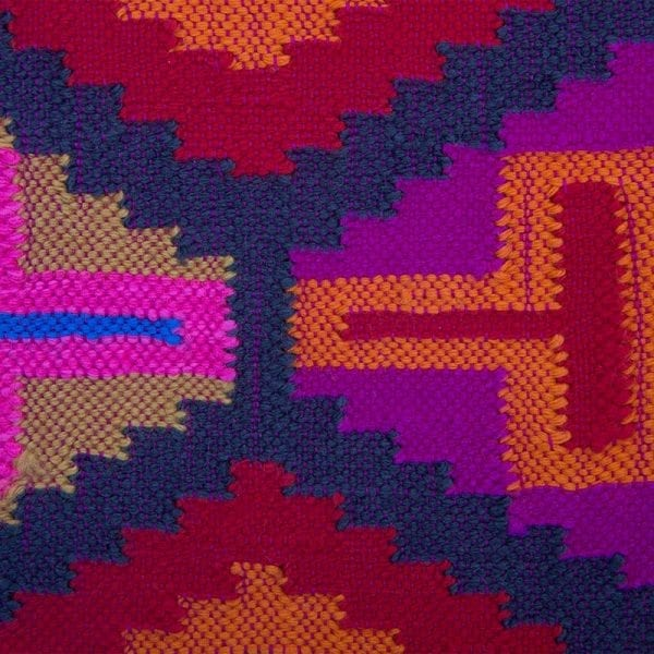 Close up detail of the soft and versatile pink and red scarf with Aztec patterning. Traditionally hand woven in South America, these scarves tell the story of culture & heritage.