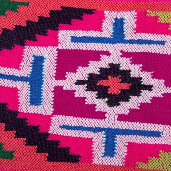 Close up detail of vibrant and beautiful hand woven pink aztec scarf. Taken from the old Nahuatl aztec language, the name Xochiquetzal means precious feather flower.
