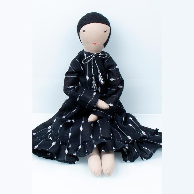 Handstitched doll in black patterned skirt and white blouse, made by women refugees from Afghanistan through Social Enterprise Silaiwali in India.