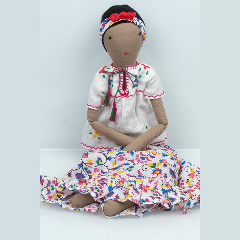 This Frida ragdoll is cute as a button, in a colourful patterned dress. Made through fair trade practices by female refugees in India.