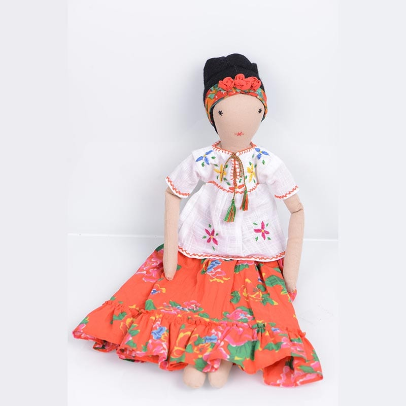 Eco friendly Frida doll comes dressed in a colourful, orange patterned skirt and white blouse. Handcrafted in India by women refugees from Afghanistan.