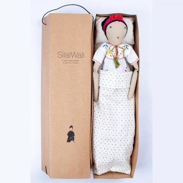 Delight your little one with an ethically made Frida doll in colourful, pink patterned skirt and white blouse. Up cycled from waste fabric in India. In soft box with bedding.